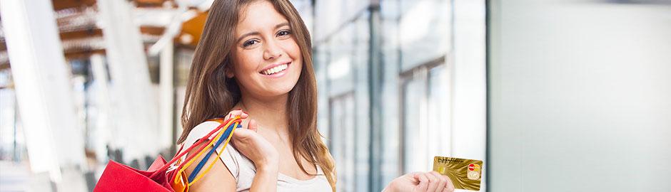 Junge Frau beim Shoppen hält MasterCard in der Hand