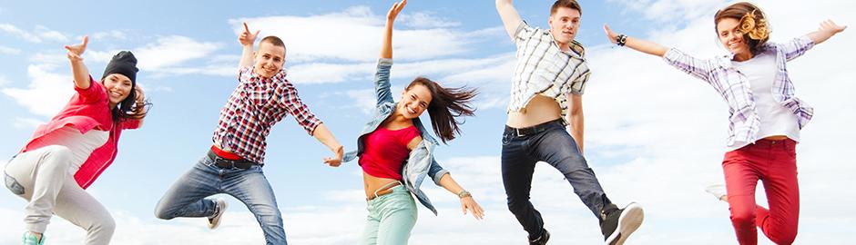 Fünf junge Menschen springen in die Luft