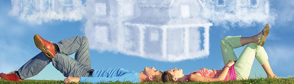 Pärchen liegt auf Wiese und sieht Wolke in Form eines Hauses