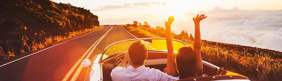 Pärchen fährt im Cabrio bei Sonnuntergang